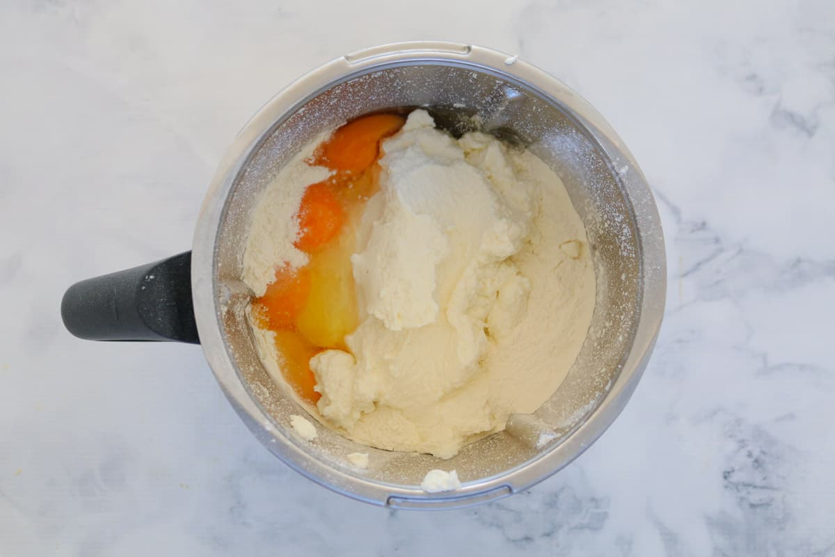 Eggs, parmesan, ricotta and flour in a Thermomix bowl.