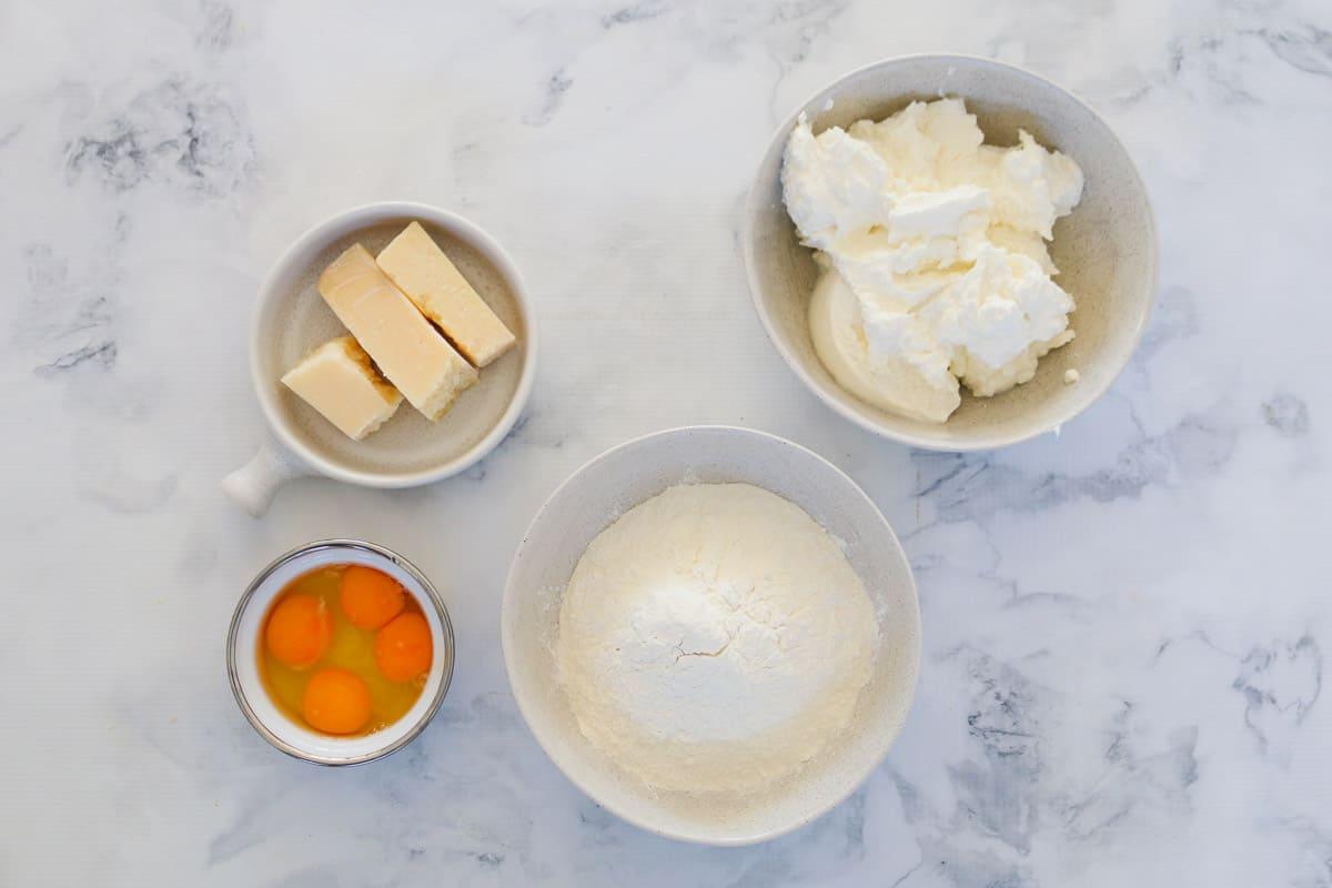 Eggs, flour, parmesan and ricotta in bowls.
