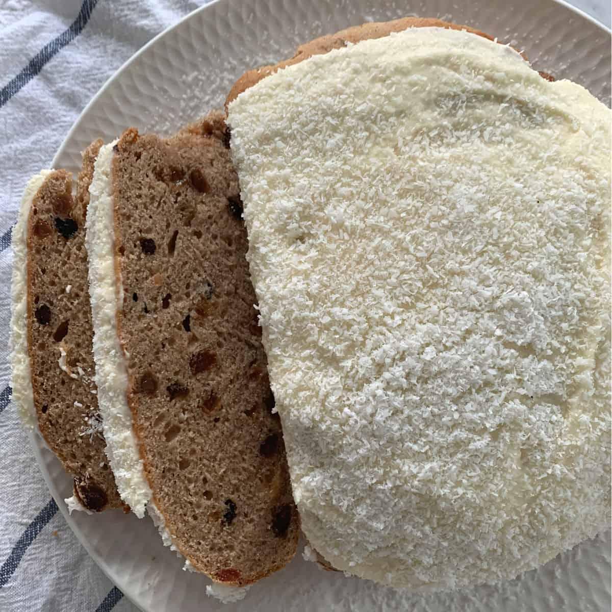 A round Boston Bun, iced and served on a plate, with two slices cut showing sultanas inside.