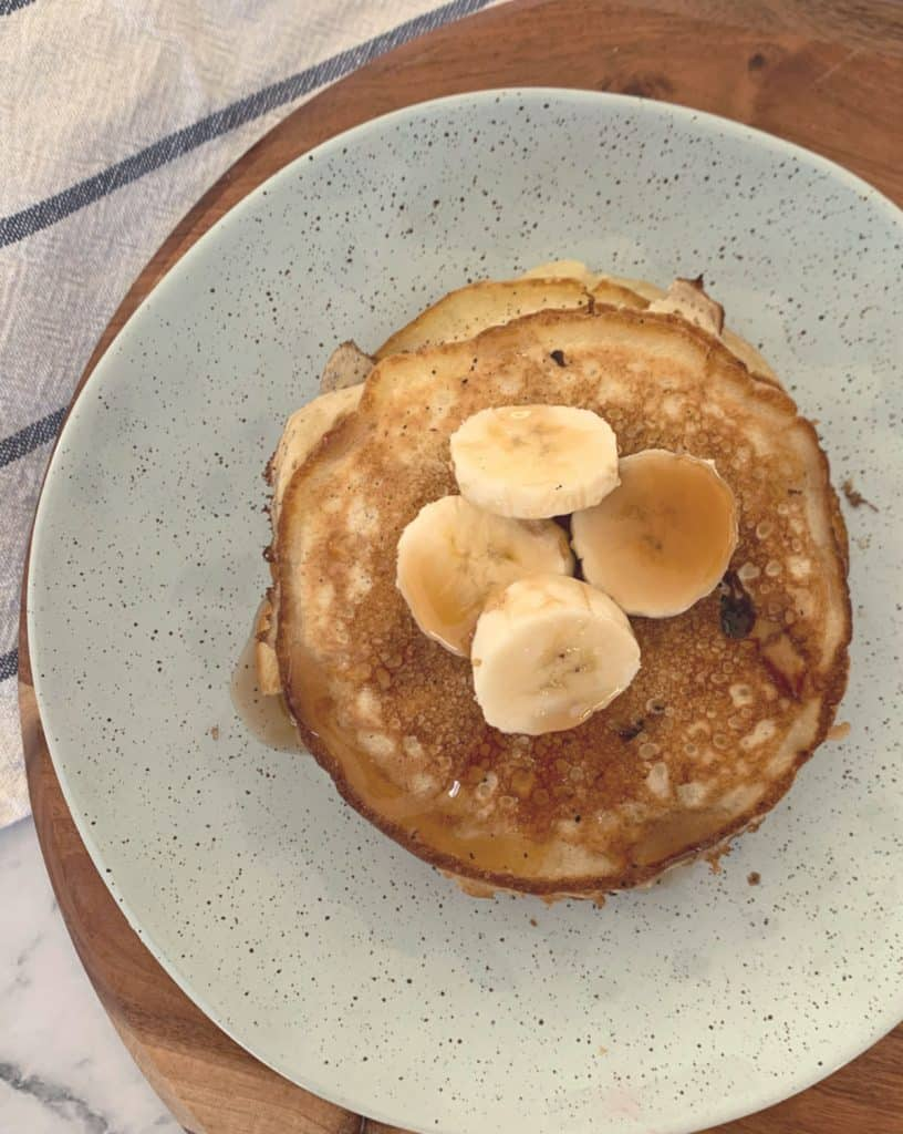 An overhead shot of banana pancakes in a bowl with slices of banana on top