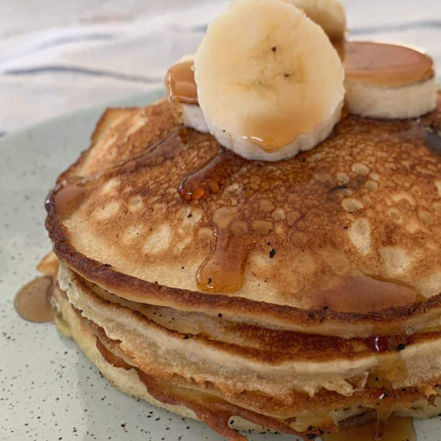 A stack of banana pancakes with sliced banana on top, and drizzled with maple syrup