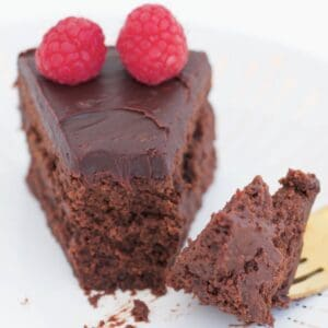 A slice of chocolate cake with a forkful removed.