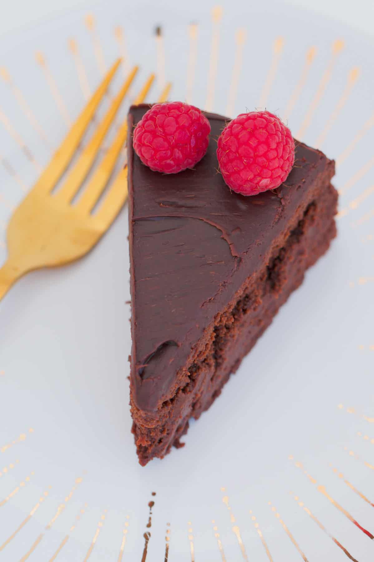 A piece of chocolate cake with ganache.