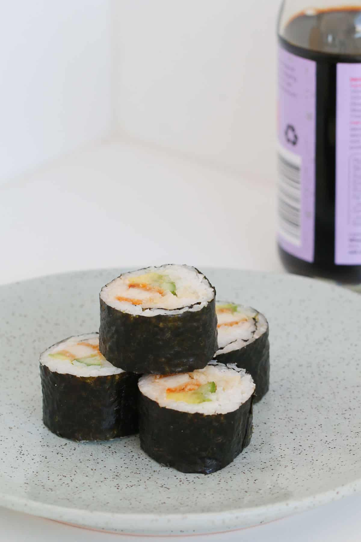 Homemade Thermomix sushi with a bottle of soy sauce in the background.
