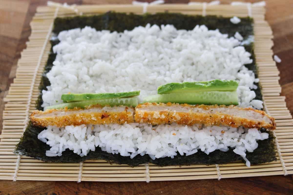 Chicken, cucumber and avocado on sushi rice on a nori sheet.