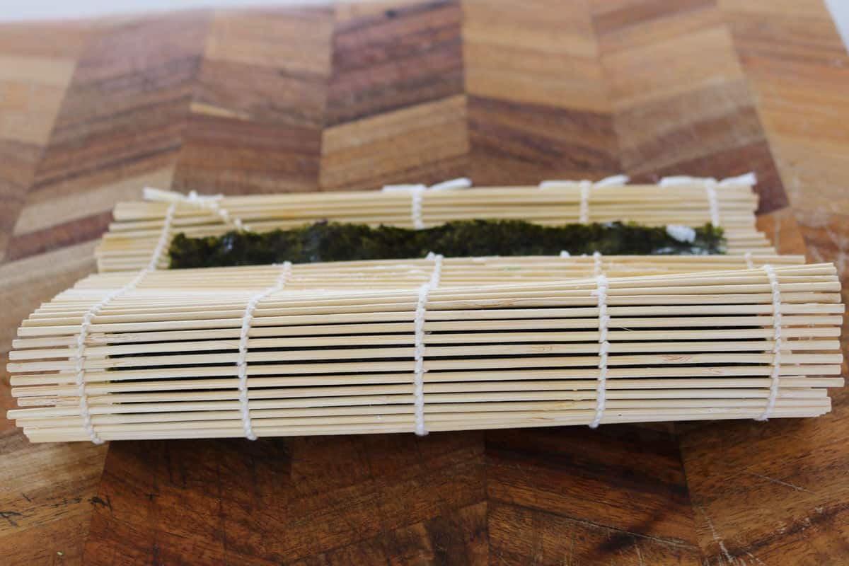 A bamboo mat rolling a sushi roll.