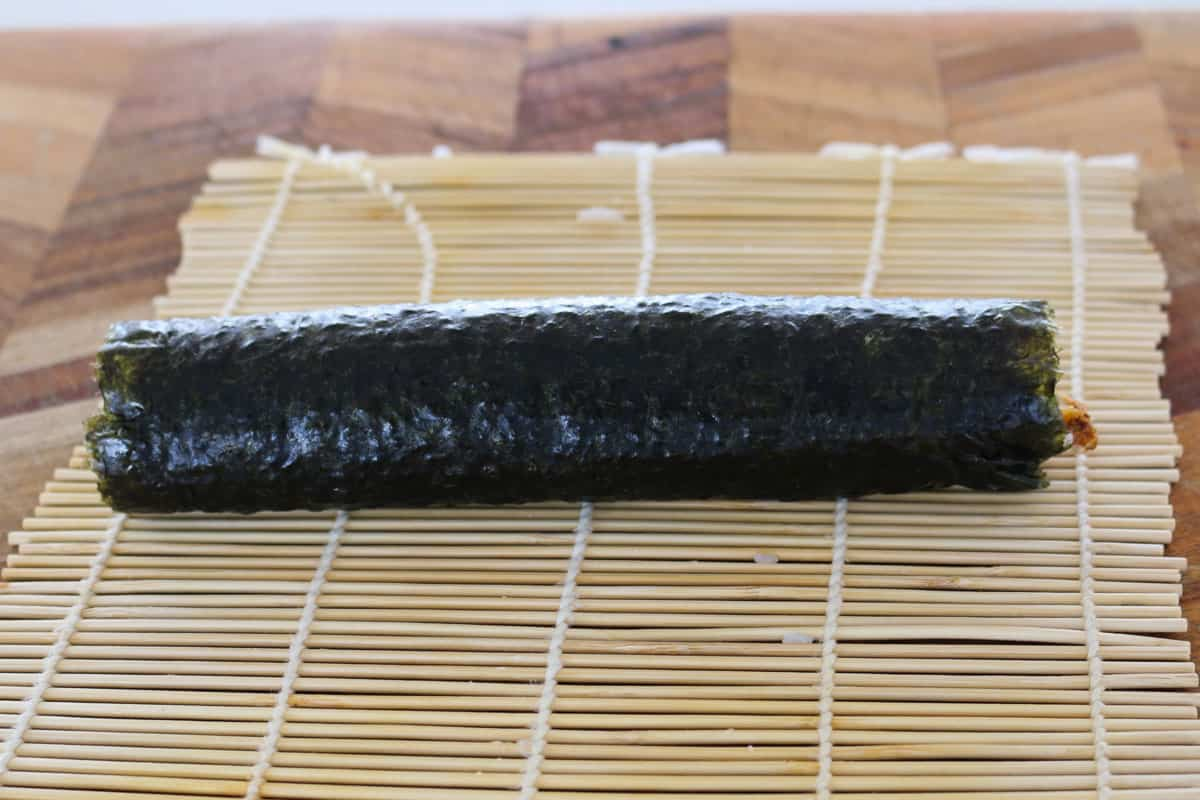 A roll of sushi being rolled on a bamboo mat.