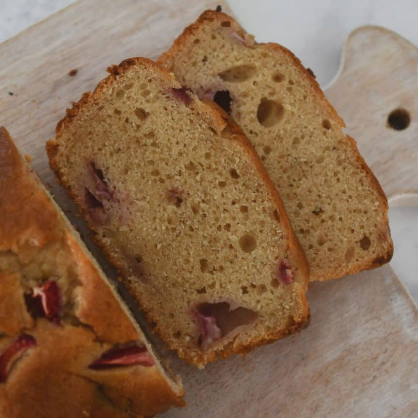 A banana and strawberry loaf with two slices cut showing strawberries baked inside.