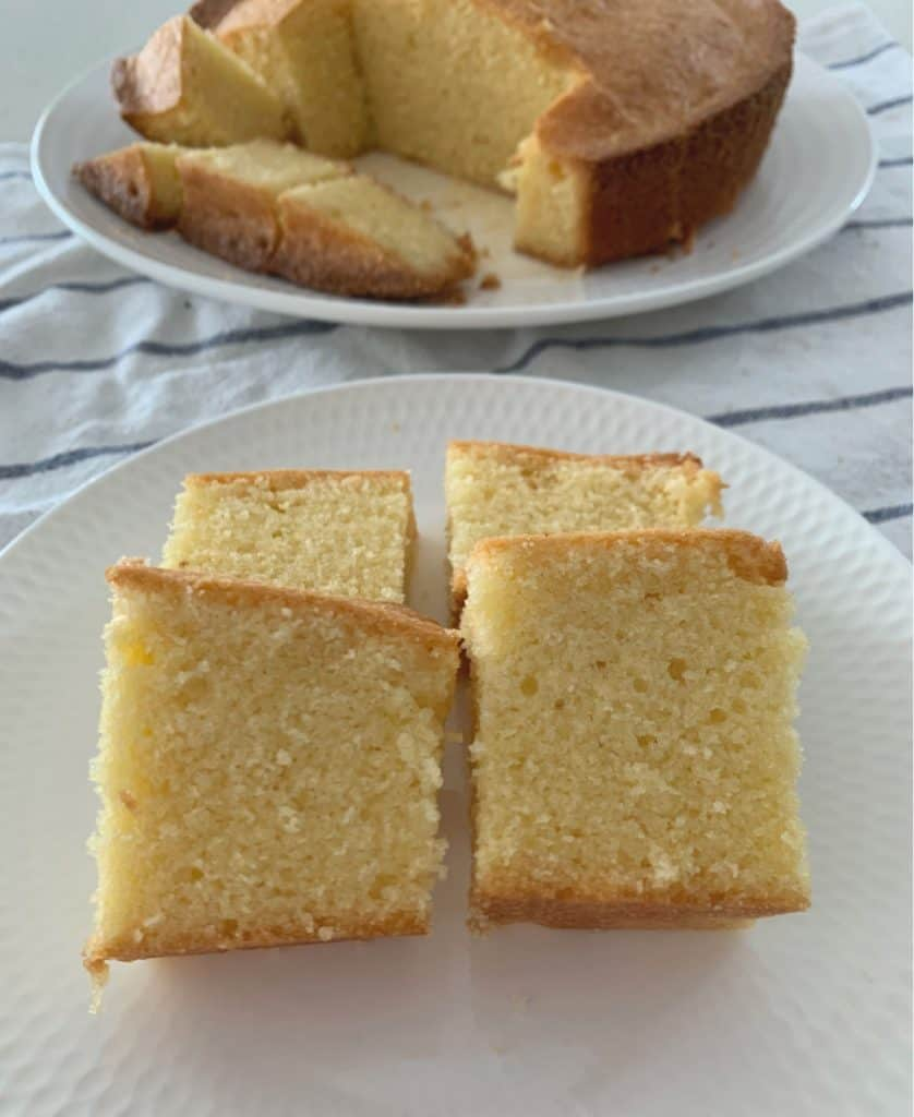 A white plate with four pieces of a plain pound cake served on it.