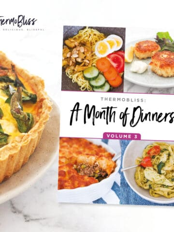 A quiche next to a 'Month of Dinners Vol 3' recipe book