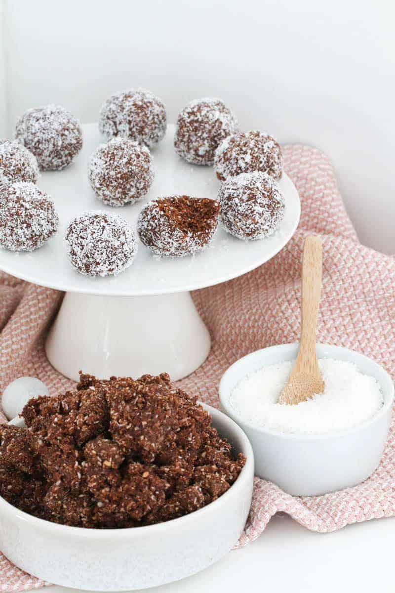 A bowl of chocolate coconut crumbs with a white plate of rum balls in the background.