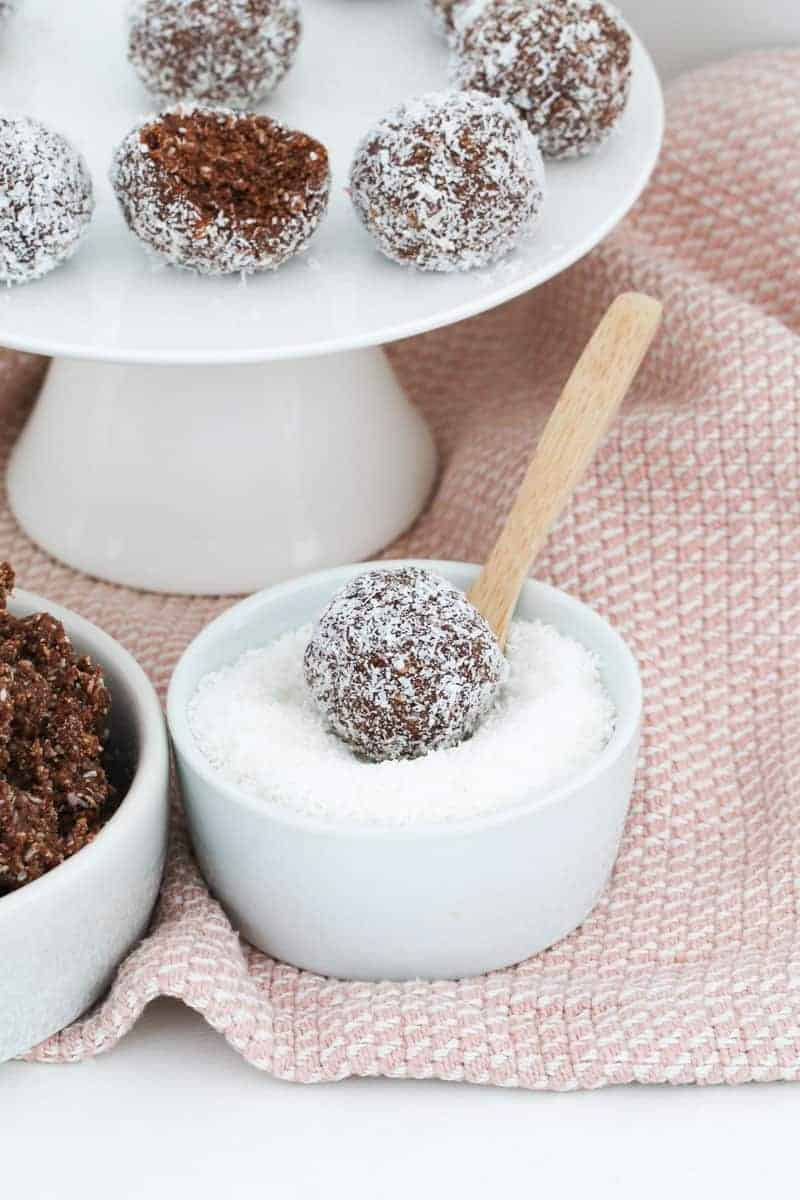A rum ball coated in coconut in a bowl of coconut.