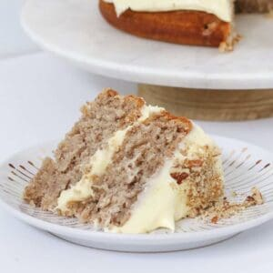 A piece of cake with cream cheese frosting.