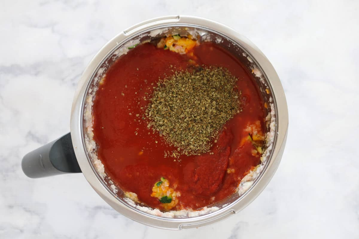 Tomato sauce and tomatoes and herbs in a Thermomix bowl.