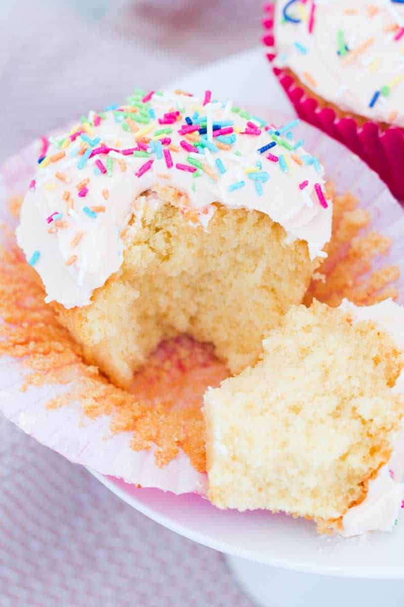 A fluffy vanilla cupcake with buttercream and sprinkles split in half.