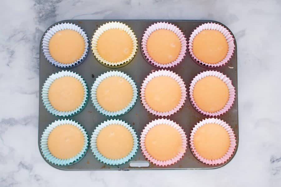 Yellow cupcake mixture divided between paper cases in a muffin tray.