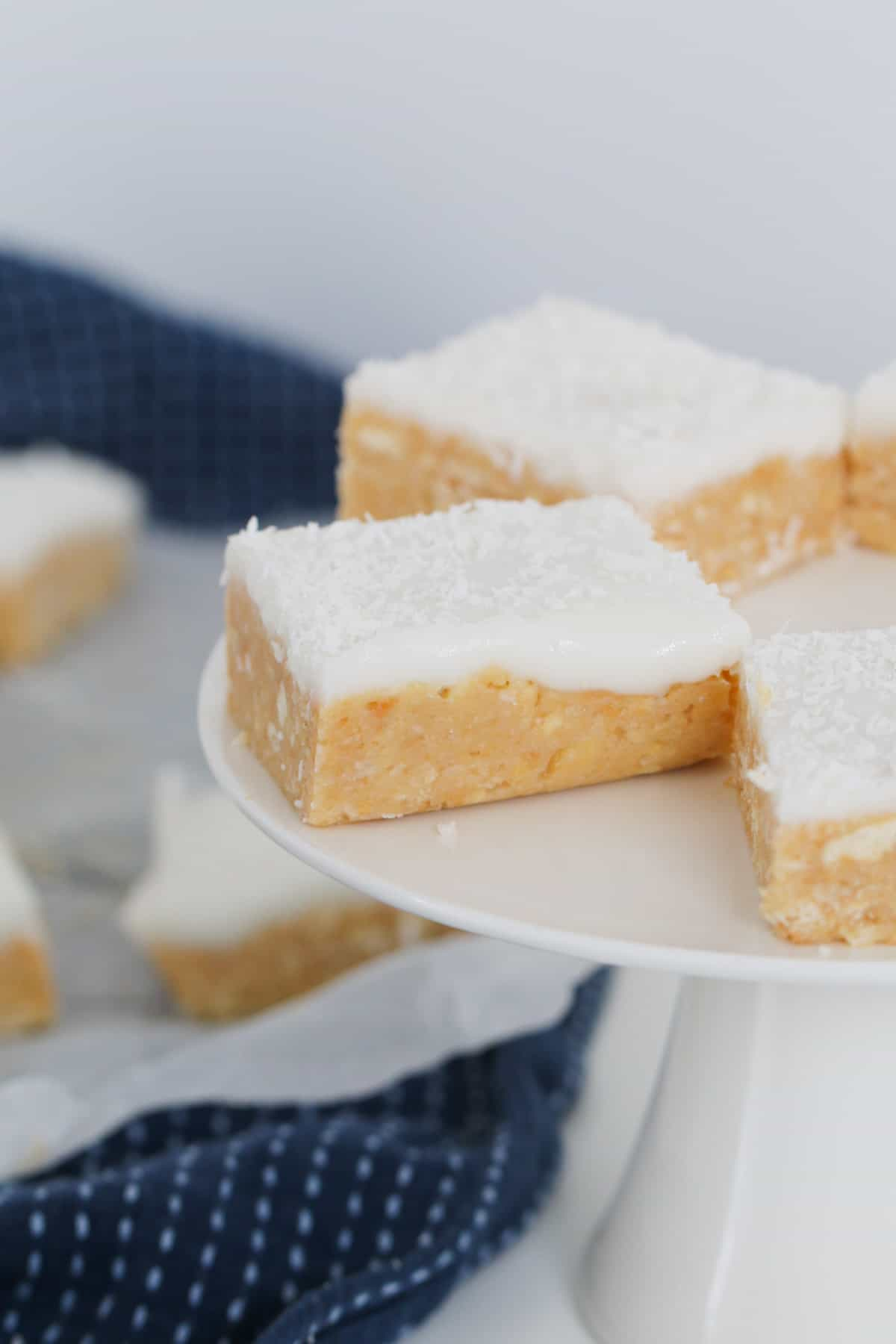 Pieces of coconut slice with lemon frosting on a cake stand.