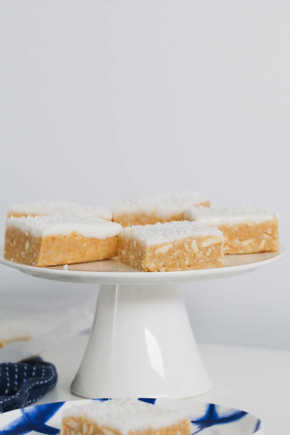 Pieces of lemon and coconut slice on a white cake stand.