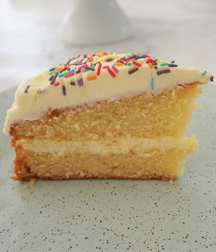 Slice of butter cake on green speckled plate