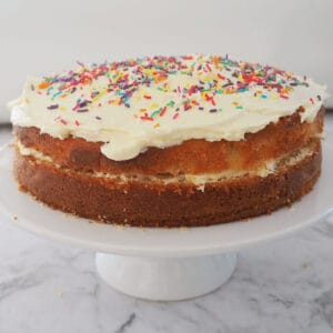 Butter cake with white buttercream on white cake stand