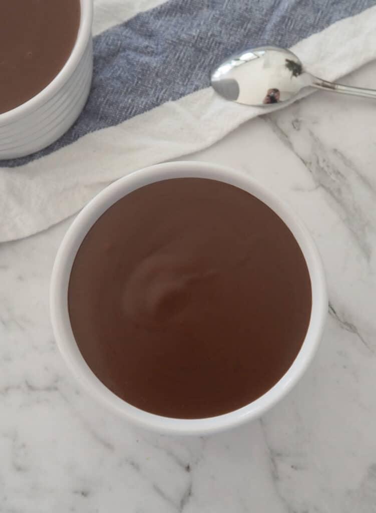 Chocolate custard in a white ramekin on marble background