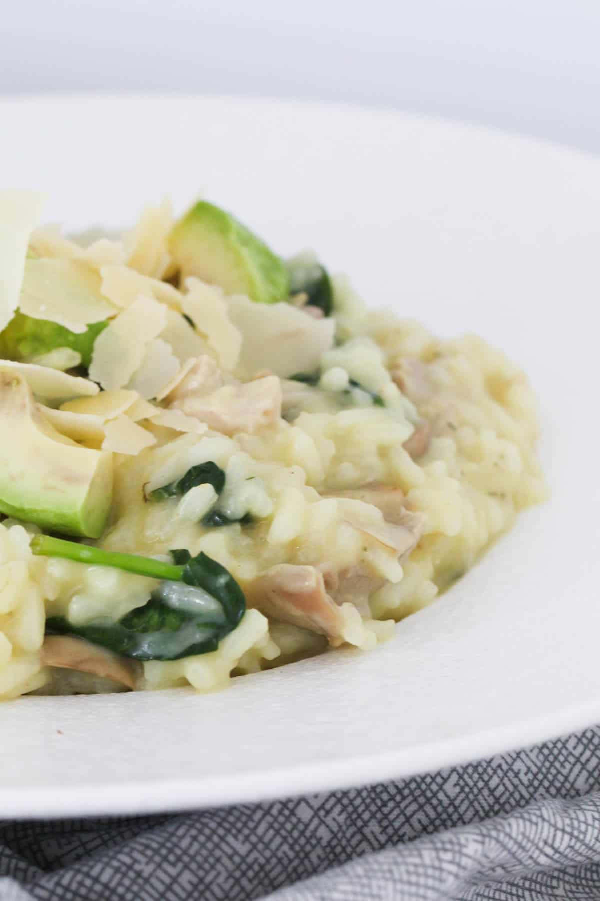 A close up of a bowl of risotto with chicken, mushrooms, spinach and avocado.