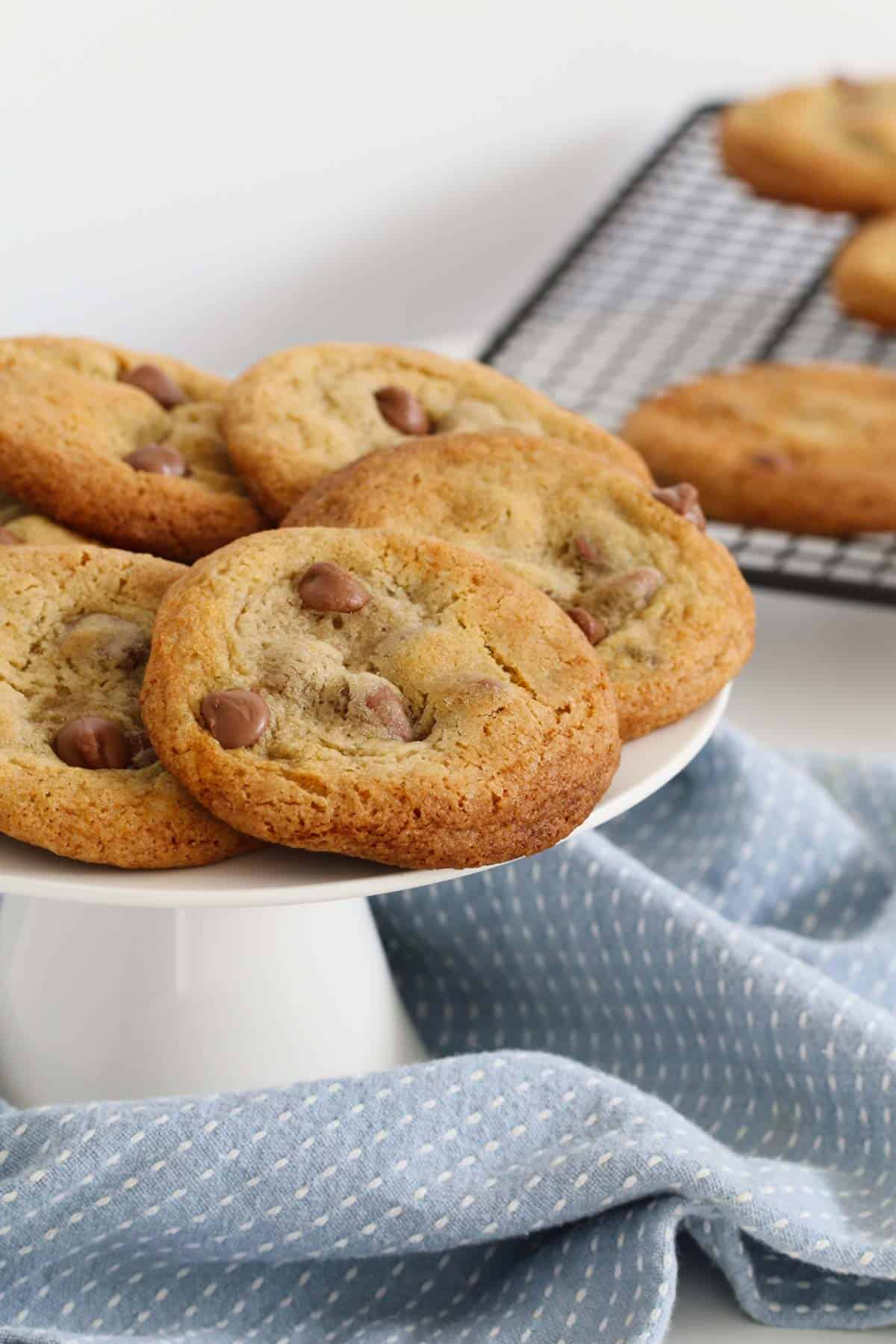 A white cake stand topped with chocolate chip cookies.
