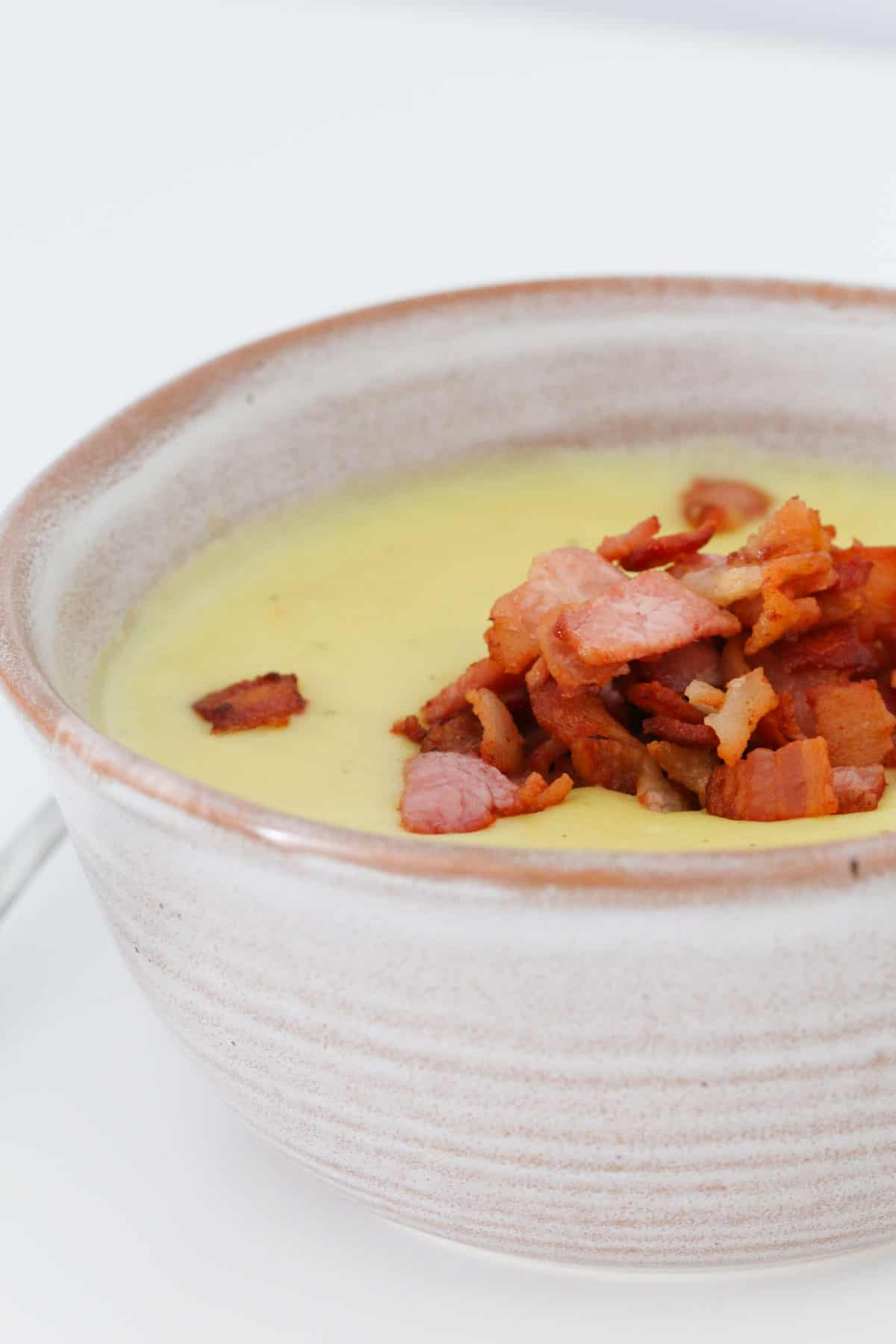 A bowl of potato and leek soup topped with crispy bacon.
